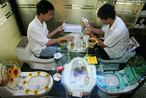 Customers play cards on toilet seats at a toilet-themed restaurant in Shenzhen